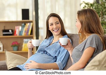 Pregnant woman talking with a friend at home
