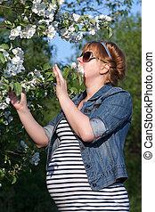 Pregnant woman touching flower