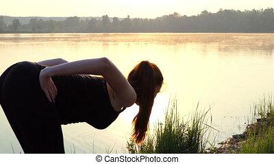 Pregnant woman trains at sunset near lake.