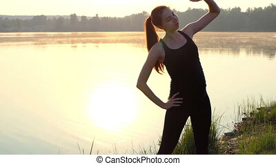 Pregnant woman trains at sunset.