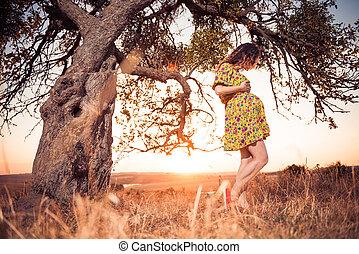 pregnant woman under tree
