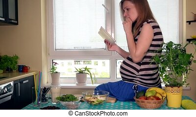 pregnant woman using tablet computer sitting on kitchen table and eating fruits