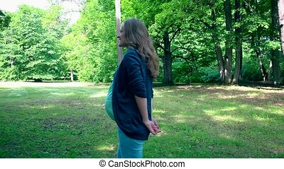 pregnant woman walking in park on summer day. Handheld...