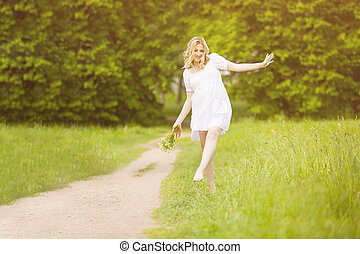 Pregnant woman walking in the park barefoot walking on carpet, holding shoes in hands