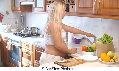 pregnant woman washing peppers in the kitchen. vegetables for salad