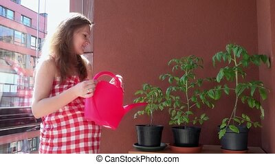 pregnant woman watering plants at flat house balcony