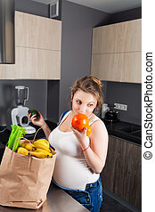 Pregnant woman with a bag of fresh fruit and vegetables