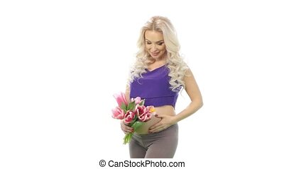 Pregnant woman with a bouquet of flowers showing tummy, white