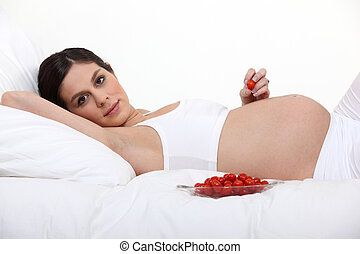 Pregnant woman with a bowl of tomatoes
