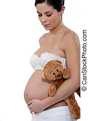 Pregnant woman with a teddy bear