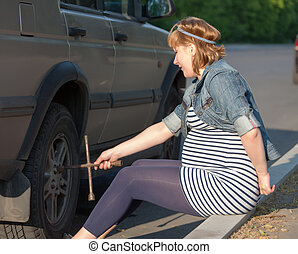 Pregnant Woman with a Wheel Brace near Car