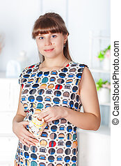 Pregnant woman with baby's bootees in her hands. Studio shot