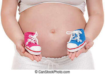 Pregnant woman with baby's bootees - Pregnant woman holding ...