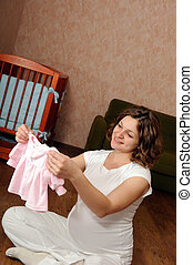 Pregnant woman with baby's clothes
