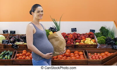 Pregnant Woman With Bag of Vegetables at Store