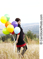 pregnant woman with balloons in grass