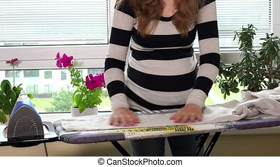 Pregnant woman with big belly and hands ironing clothes on...