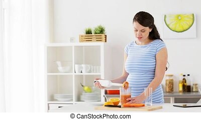 pregnant woman with blender cooking fruits at home