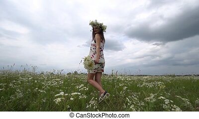 Pregnant woman with bouquet of camomile flowers.