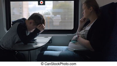 Pregnant woman with child having train journey