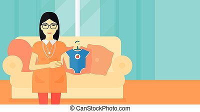 Pregnant woman with clothes for baby.