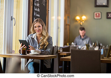 Pregnant Woman With Digital Tablet At Table