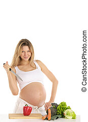 pregnant woman with fruits, vegetables and knife
