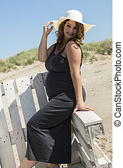 pregnant woman with hat on wooden chair