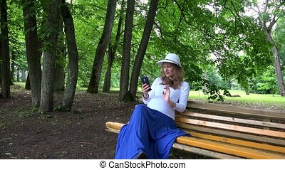 Pregnant woman with hat take selfie photo sitting in park on...
