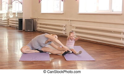 Pregnant woman with her first kid daughter doing gymnastics