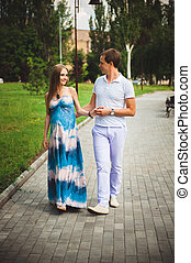 Pregnant woman with her husband in the park.