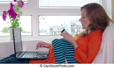 Pregnant woman with laptop computer and credit card shopping baby clothes online