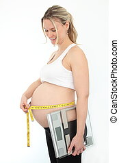 Pregnant woman with measering tape and level