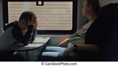 Pregnant woman with son traveling by train
