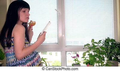 Pregnant woman with tablet computer eating cake on window background