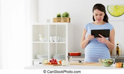 pregnant woman with tablet pc cooking at home