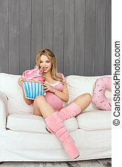 Pregnant woman with toys of ice cream posing indoors at home. Heath care and food consept.