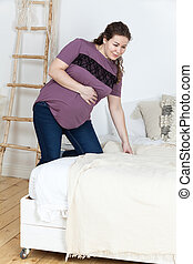 Pregnant woman with utering colic holding her nelly and sitting on the bed, tired and unhappy