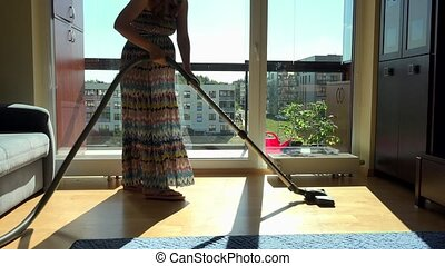 Pregnant woman with vacuum cleaner hoover room in front of...