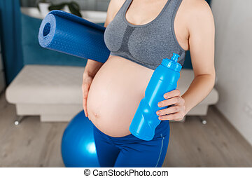 pregnant woman with yoga mat and bottle of water