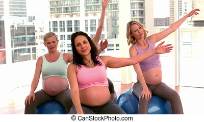 Pregnant women doing yoga in fitnes