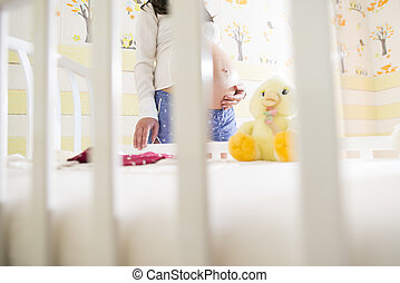 Pregnant women in a baby room.