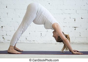 Pregnant young woman doing prenatal downward facing dog pose...