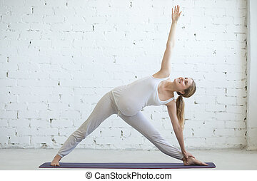 Pregnant young woman doing prenatal yoga. Extended triangle ...