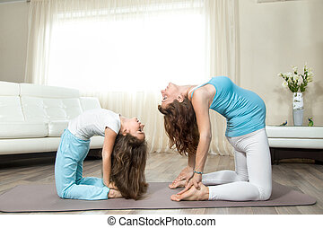 Pregnant young woman doing prenatal yoga with her little daughter