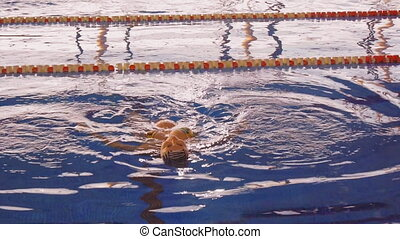 Pregnant young woman floating backstroke