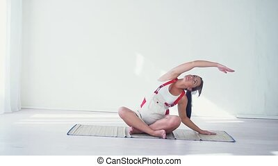 Pregnant young woman in all fours position exercising on...