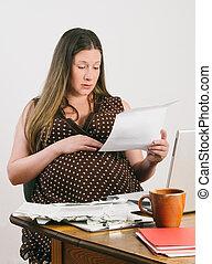 Pregnant Young Woman Paying Bills at Laptop Computer