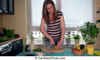 Pregnant young woman preparing cutting pear fruit in kitchen at home