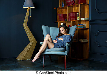 pregnant young woman sitting in a chair